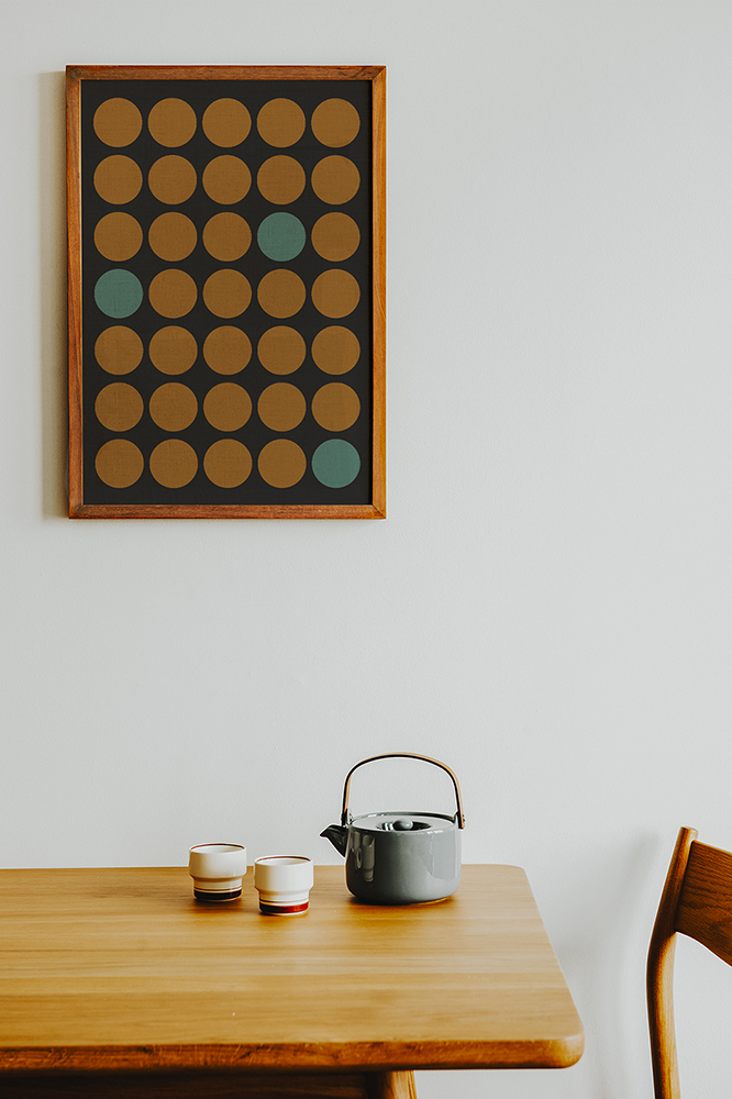 32 counties ireland art print - mustard circles on a black background with three turqouise coloured circles- art print hanging on a wall on the kitchen above a table with a wooden chair and a teapot on the table