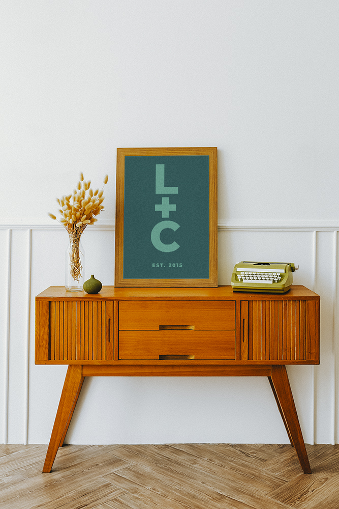 Picture frame with personalised name art on a wooden sideboard table with hare tail grass and a typewriter
